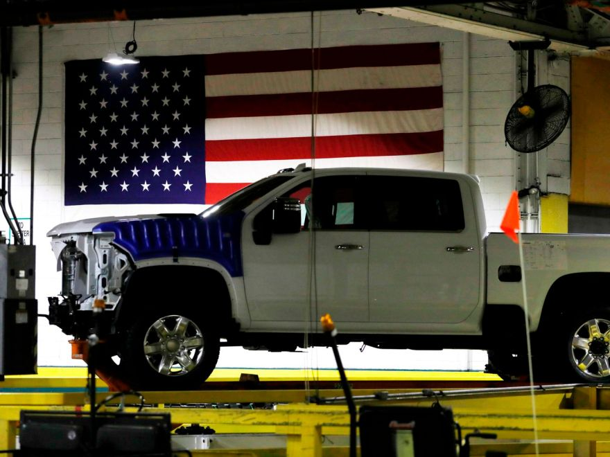 A Chevy truck is half assembled and sitting in front of an American flag in Flint, Michigan.