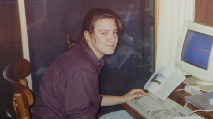 A woman hunches over an old computer