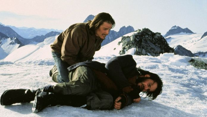 Ethan Hawke in Alive crouches in the snow over a fellow survivor who's curled up in pain.