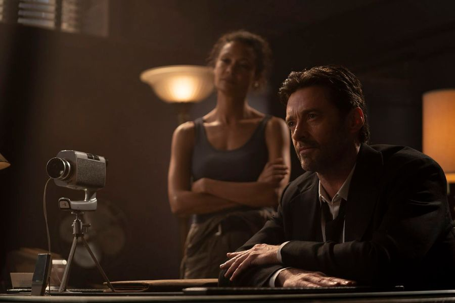 Hugh Jackman sits at a table with a video camera pointed at his offscreen subject while Thandiwe Newton stands behind him in Reminiscence