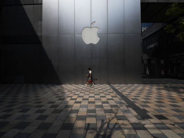 A woman walks past an Apple store in Beijing, China.