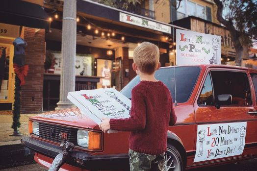 A pop culture food pop up featuring a red car and branded pizza boxes.