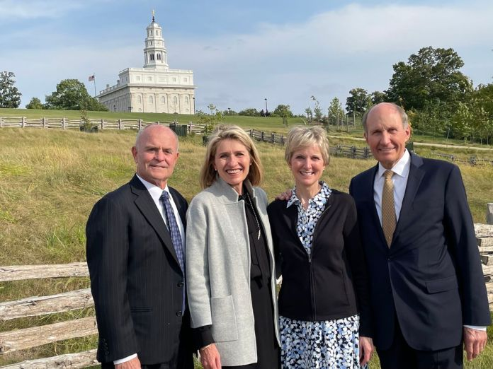 Two couples pause for a photo with the Nauvoo Illinois Temple in the background.