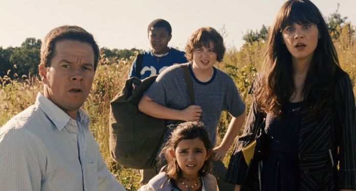 Mark Wahlberg, Zooey Deschanel, and other cast members in The Happening stand in a field of yellow grass, looking horrified at something offscreen.
