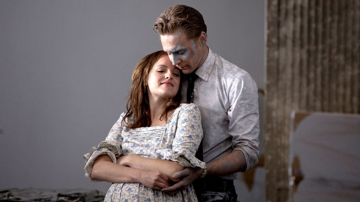 Tom Hiddelston as Robert Laing holding his wife while covered in paint.