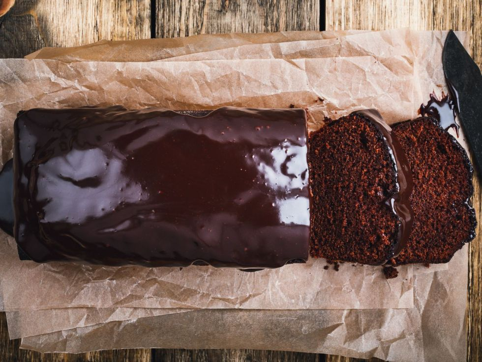 Overhead image of glazed chocolate loaf cake on wooden board, two slices cut to show interior of cake.