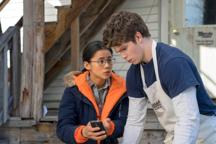 a young woman and a young man look at a phone