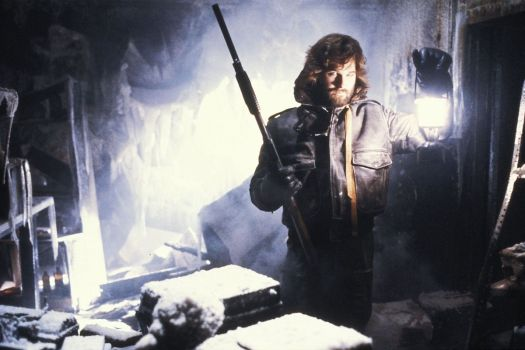 Kurt Russell holds up a lantern in a frosty room