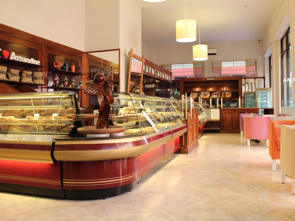 A long, curved, lit pastry case inside an airy patisserie with pendant lighting, marble floors, and wooden shelves behind the counter displaying products and brand signage.