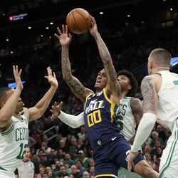 Utah Jazz's Jordan Clarkson (00) passes the ball off in traffic during the first quarter of an NBA basketball game against the Boston Celtics, Friday, March 6, 2020, in Boston.