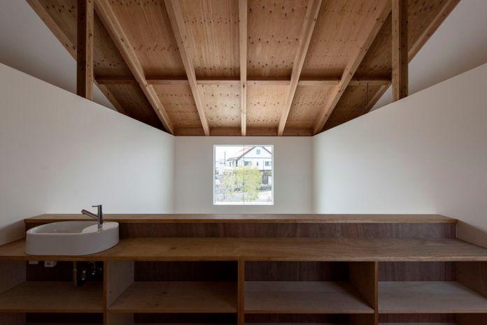 Под деревянными потолками, лофт пространство имеет раковину и деревянные стойки с видом на большое окно картины.