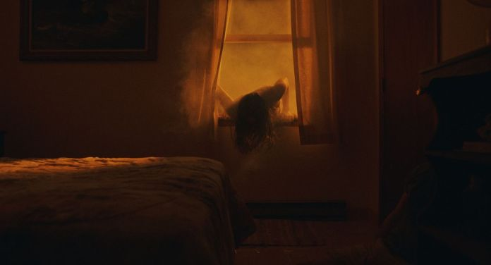 A dark-haired woman crawls through an open window into a room lit by an eerie yellow-orange light in The Beach House.