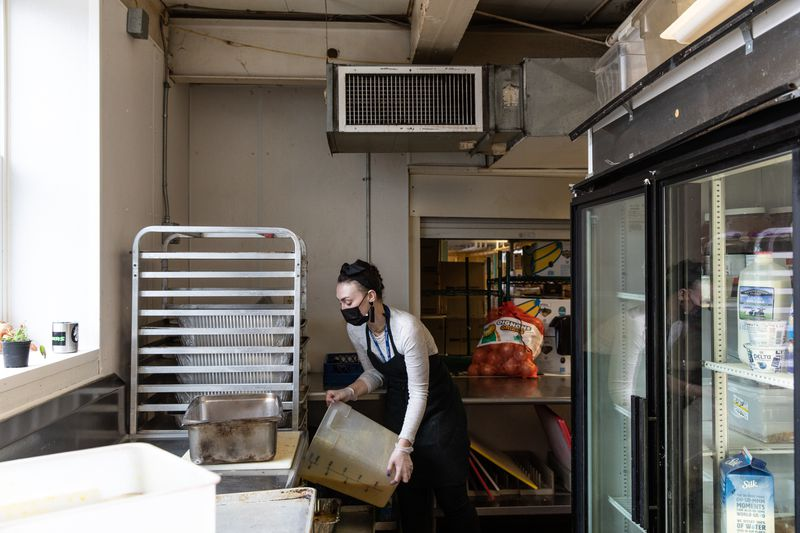 A woman lifts a large bucket with dry ingredients in a large kitchen space