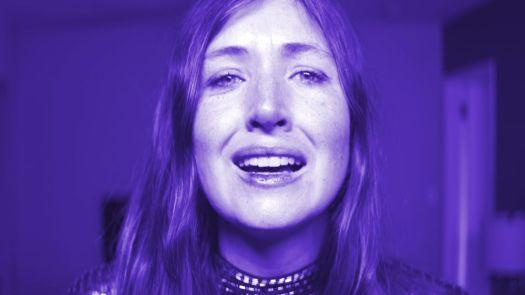 Kate Lyn Sheil in close-up purple light in She Dies Tomorrow