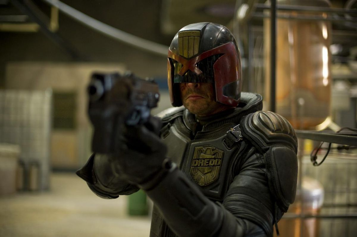 Karl Urban (Dredd) aims his pistol in Pete Travis' Dredd (2012)