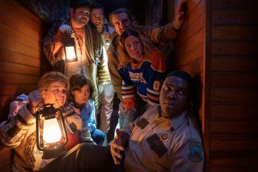 Seven of Werewolves Within's cast members huddle together nervously, clutching lanterns