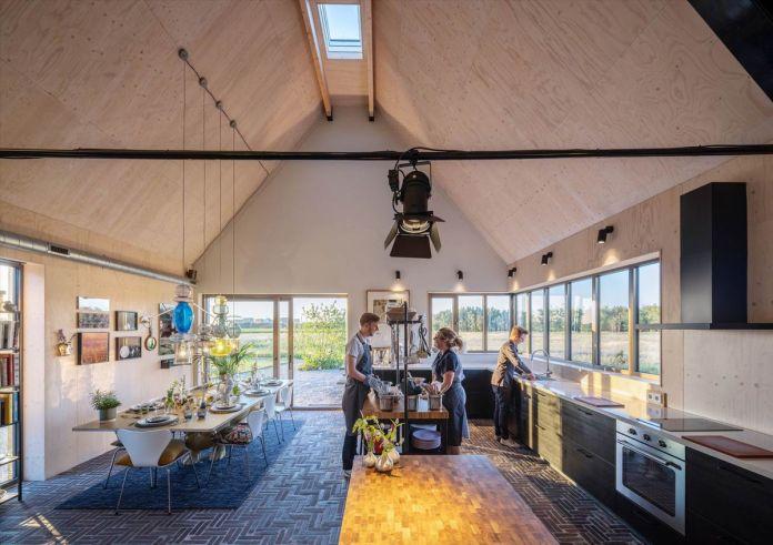 Люди готовят в кулинарной студии под остроконечной крышей, с обеденной зоной слева и кухней справа.