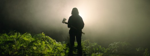 A silhouetted figure in the forest, clutching an axe, in In the Earth