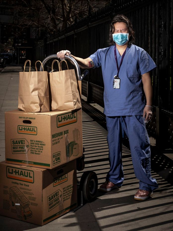 Surgical technician Henry Chung received a box of food while wearing scrubs and facial masks