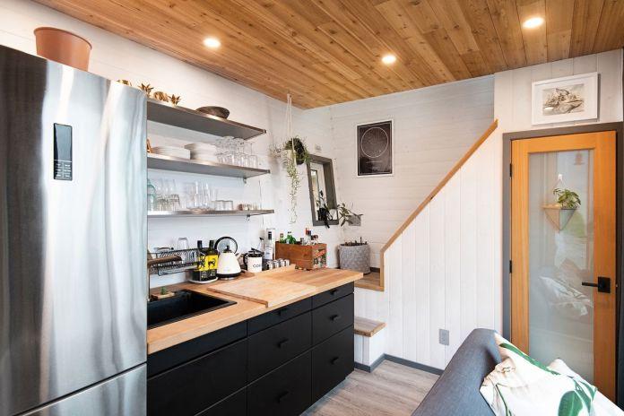 Кухня оснащена деревянными столешницами, черным краснодеревщиком и холодильником из нержавеющей стали. В углу лестница ведет в спальню на чердаке.