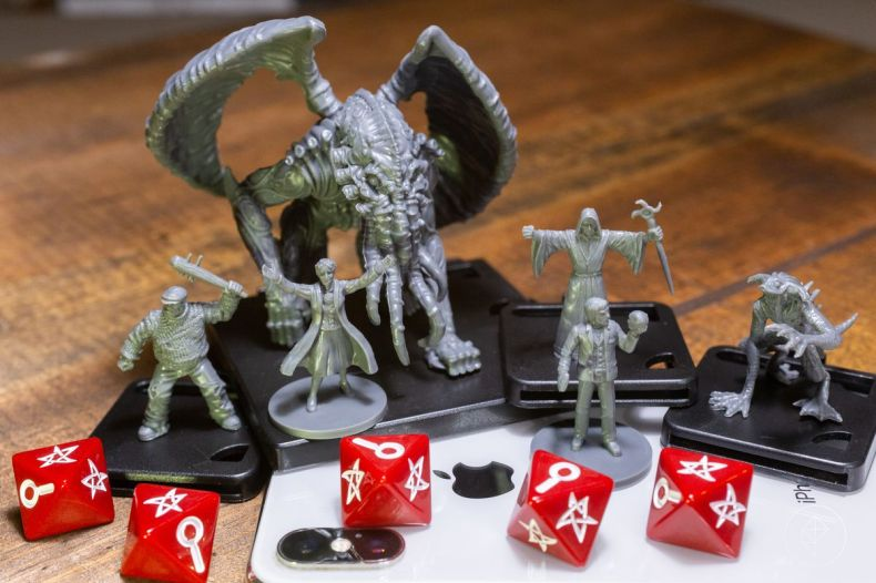 Miniatures of an Elder God and several smaller minions, plus a pair of heroes, standing on an iPhone.