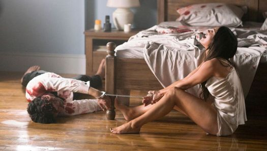 Megan Fox, in a silk camisole and underwear, weeps on the floor at the foot of a bed while handcuffed to the corpse of a bloody man in Till Death.