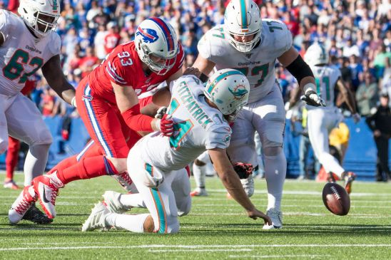 Miami Dolphins quarterback Ryan Fitzpatrick fumbles the ball as Buffalo Bills defensive end Trent Murphy and offensive guard Jesse Davis go for the ball in the fourth quarter at New Era Field.