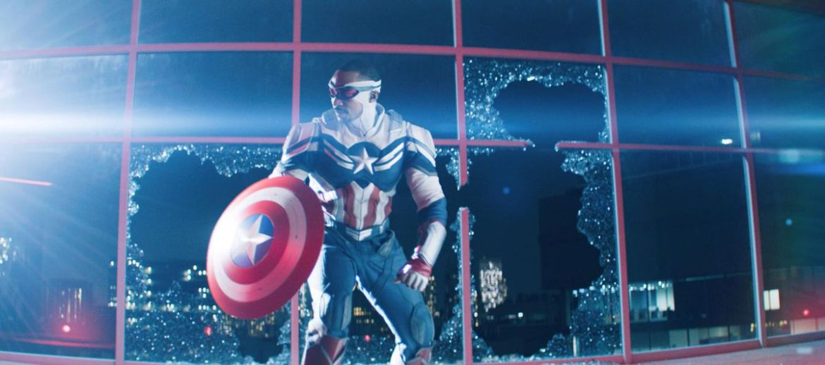 Anthony Mackie as new Captain America crouches in front of some shattered windows