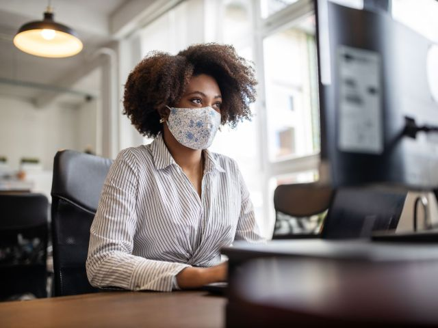 Person wearing a face mask working at a desk looking at computer monitor in an office.