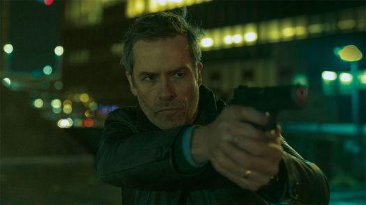 Guy Pearce as David Carmichael aiming a pistol in Zone 414.