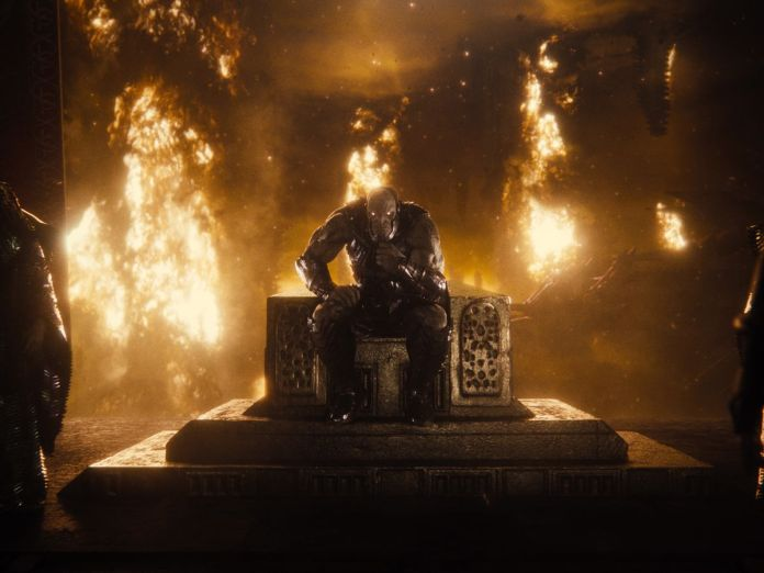 The alien villain Darkseid sits on a throne in a burning room in Zack Snyder's Justice League