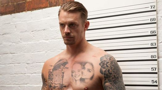 A shirtless, heavily tattooed Joel Kinnaman stands in front of a wall with height measurement in The Informer