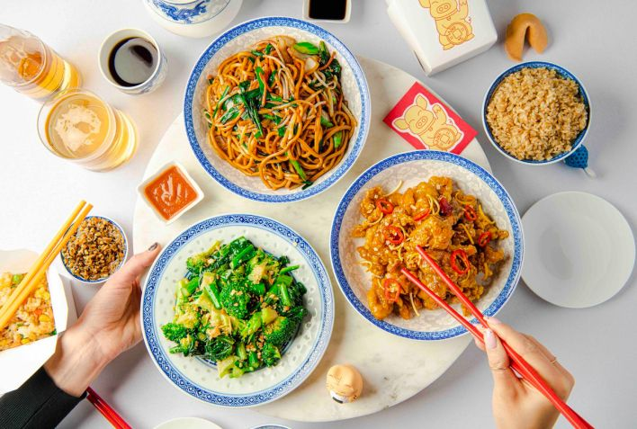 A spread of dishes from Lazy Susan: chow mein, stir-fried broccoli, and orange chicken