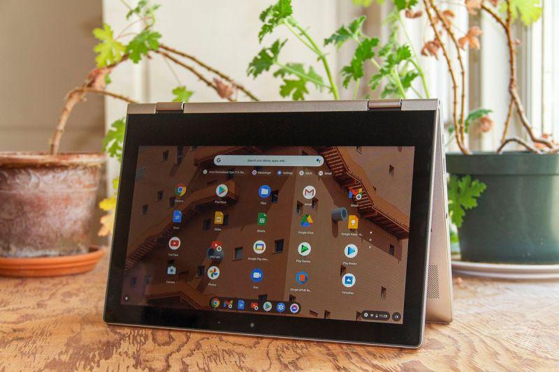 Il Chromebook Lenovo Ideapad Flex 3 in modalità tenda, con lo schermo rivolto verso la fotocamera, leggermente inclinato a sinistra, si trova su un tavolo con due piante d'appartamento sullo sfondo.  Lo schermo mostra una griglia di icone delle app di Chrome OS.