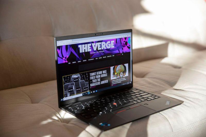 Il ThinkPad X1 Nano è seduto su un divano, leggermente inclinato a destra, aperto.  Lo schermo visualizza la homepage di The Verge.