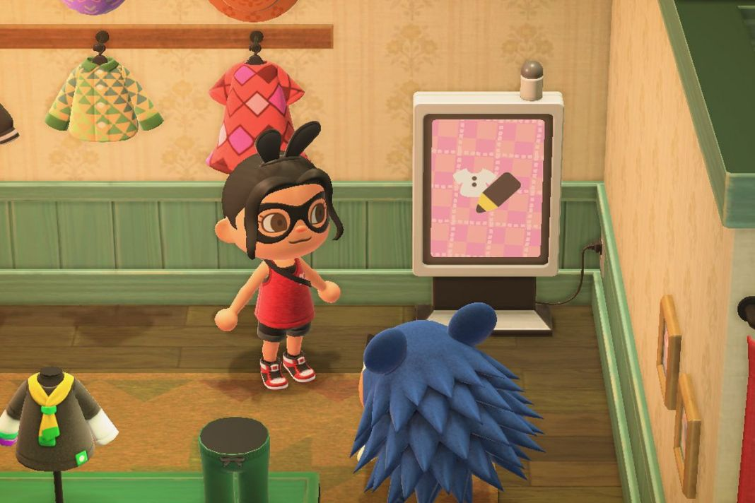 An Animal Crossing character stands next to a large screen in the tailor's shop