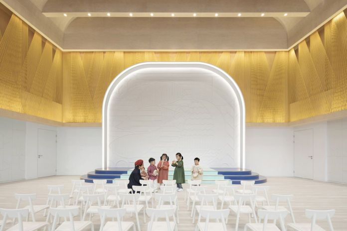 Дети в комнате со сценой, белыми стульями и золотой обработкой стены в задней части.
