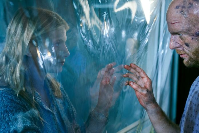 Mélanie Laurent reaches her hand toward a wounded, dirty man on the other side of a sheet of plastic in Oxygen