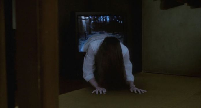 A figure in white crawling out of a TV