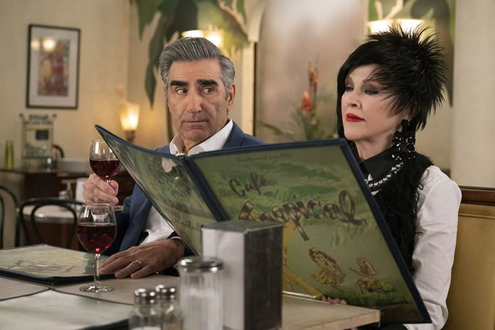 Dan Levy holding a glass of wine while Catherine O'Hara, wearing a feathered hat, reads a menu