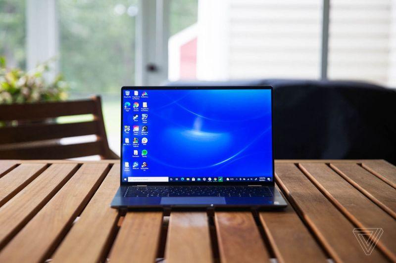 Il Dell Latitude 9420 si apre su un tavolo in veranda in legno.  Lo schermo mostra uno sfondo blu del desktop.