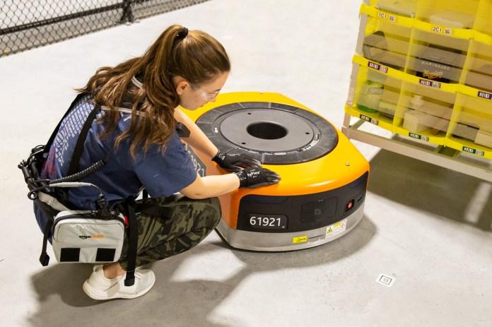 Un empleado de Amazon que usa el Robotic Tech Vest inspecciona un robot de almacén.