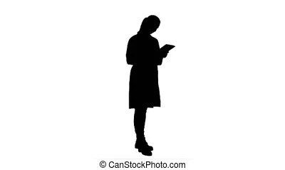 Silhouette young female doctor examining xray writing down