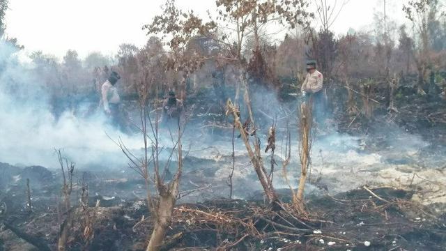 Polisi berada di kebakaran lahan untuk memadamkan titik api.