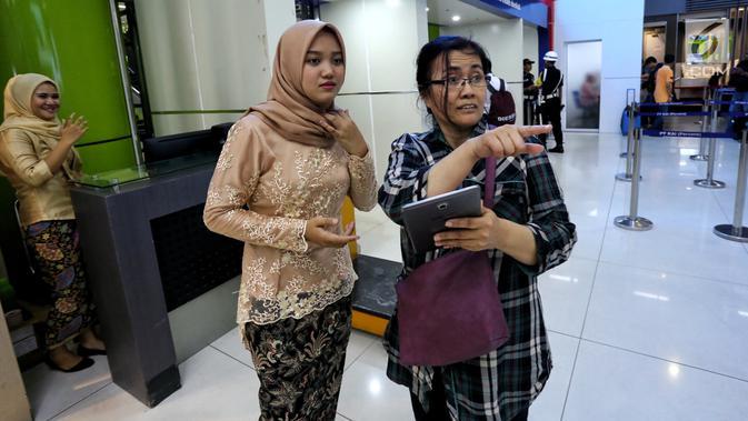 Petugas frontliner berpakaian tradisional membantu calon penumpang di Stasiun Gambir, Jakarta, Minggu (21/4). PT KAI Daop 1 Jakarta mewajibkan petugas frontliner wanita dan pria mengenakan kebaya dan batik untuk menyambut Hari Kartini. (Liputan6.com/Johan Tallo)