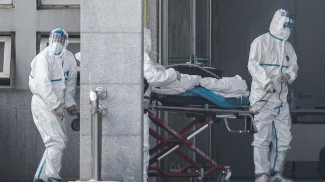 Staf medis memindahkan seorang pasien dari ambulans ke rumah sakit Jinyintan, tempat pasien-pasien terinfeksi virus corona dirawat di Wuhan, provinsi Hubei, China pada Senin 20 Januari 2020.