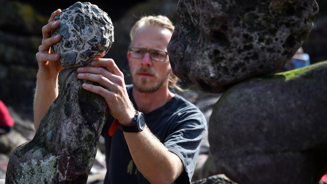 Philip Wachmann dari Austria berkompetisi dalam Kejuaraan Menumpuk Batu Eropa 2019 di Dunbar, Skotlandia, Minggu (21/4). Pemenang dalam kejuaraan tersebut akan terbang ke llano Earth Art Festival dan mengikuti World Stone Balancing Competition 2020. (Andy Buchanan / AFP)