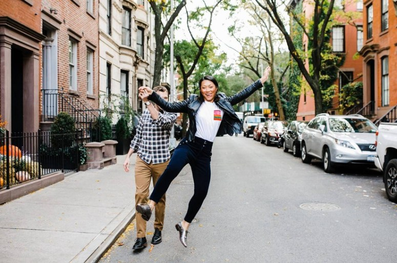 couple walks down a residential street in NYC with brownstone townhouses on both sides. She is jumping in the air while holding his hand