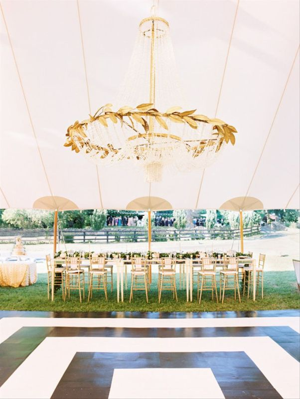 wedding reception tent with crystal chandelier with gold leaves