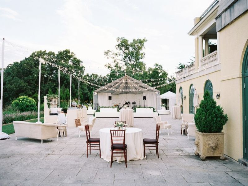 outdoor wedding reception venue with bistro lights and round tables